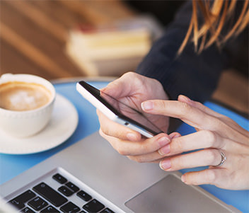 Young lady reading news on her smartphone in a café